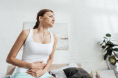 Fotografie Low-Winkel-Ansicht der gestressten jungen Frau mit Magenschmerzen