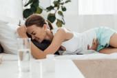 Leidende Frau im Bett und Tabletten mit Wasserglas im Vordergrund