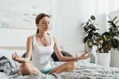 verärgert junge Frau sitzt auf dem Bett in Lotus-Pose mit geschlossenen Augen