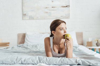 Pensive young woman eating green apple in bed stock vector