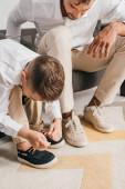ostříhané zobrazení otce učit syna, aby uvázal tkaničky doma