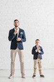 full length view of father and son in jackets with boutonnieres