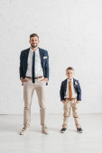 pohled plný délky otce a syna v kabátě s květiny