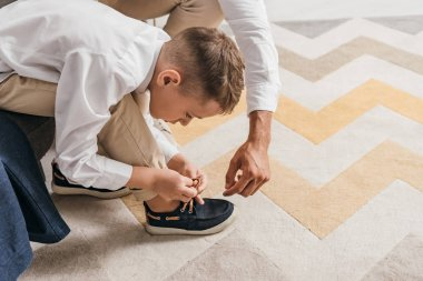 partial view of father teaching son to tying shoelaces at home