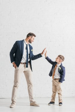 Full length view of father and son in jackets with boutonnieres looking at each other stock vector