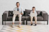Vater und Sohn in offizieller Kleidung mit Laptop und Musik über Kopfhörer auf dem Sofa