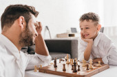 Photo dad and son playing chess together at home