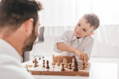 Photo selective focus of dad and son playing chess together at home