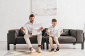 Sohn und Vater in festlicher Kleidung sitzen auf dem Sofa und lesen Zeitung