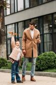 Plná délka pohled na usmívajícího se otce s jednorázovým šálkem kávy a synem s hrací plochou na ulici