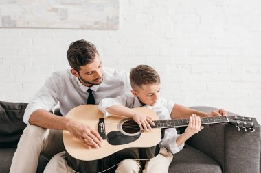 dad teaching son to play acoustic guitar at home