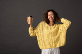happy curly woman in yellow knitted sweater with closed eyes holding coffee to go on black background