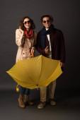 boldog stílusos Interracial pár ősszel ruhát sárga esernyő, fekete háttér