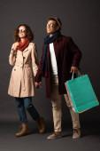 sorridente elegante coppia interrazziale in autunno vestito tenendo le mani e borse della spesa su sfondo nero