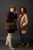 Fotografie stylish interracial couple in autumn outfit with bags on black background