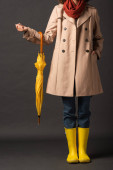 Photo cropped view of woman in trench coat and rubber boots holding yellow umbrella on black background