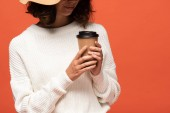 cropped view of woman in hat holding coffee to go isolated on orange
