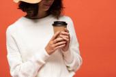 oříznutý pohled ženy v klobouku s kávou, která má jít izolovaně na oranžovém