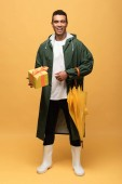 Mischling in Regenmantel und Gummistiefeln mit Geschenkbox und Regenschirm isoliert auf gelb