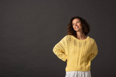 Happy curly woman in yellow knitted sweater looking away on black background stock vector
