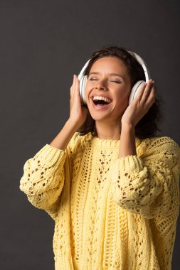 Happy curly woman with closed eyes in yellow knitted sweater listening music in headphones on black background stock vector