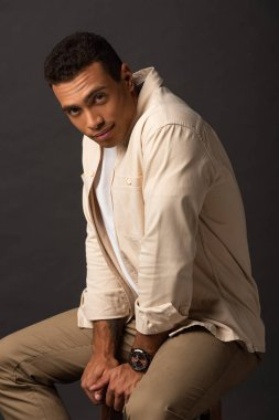 handsome mixed race man in beige shirt sitting on chair on black background