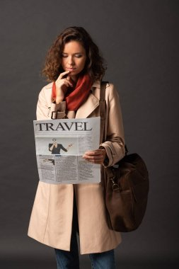 Dreamy woman in trench coat with leather bag reading travel newspaper on black background stock vector