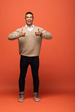 Happy mixed race man in beige sweater showing thumbs up on orange stock vector