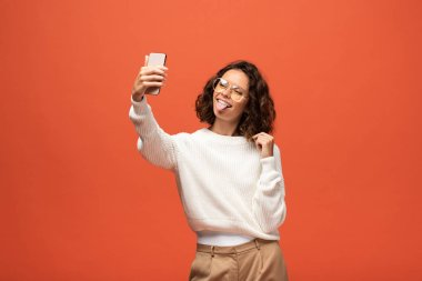 Woman in autumnal outfit and glasses showing tongue while taking selfie isolated on orange stock vector