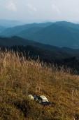 žlutá louka s ječným kolem batohu v horách proti obloze