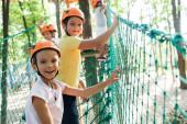 selektivní zaměření veselého a roztomilé dítě na vysoké lanové stezce s multikulturními přáteli