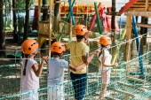 cute multiethnic kids in orange helmets on high rope train