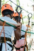 selective focus of african american kid near friend with safety equipment and helmet