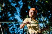 Blick auf das niedliche Kind in orangefarbenem Helm draußen