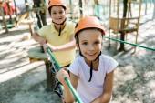 selektiver Fokus des entzückenden Kindes im Helm nahe Freund mit Höhenausrüstung im Abenteuerpark