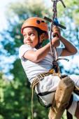 Fotografie entzückendes afrikanisch-amerikanisches Kind mit orangefarbenem Helm im Abenteuerpark