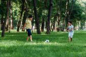 Fotografie Niedliche multikulturelle Jungs spielen Fußball auf grünem Rasen