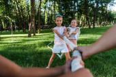 Fotografie Selektiver Fokus fröhlicher multikultureller Kinder, die im Tauziehen draußen gegeneinander antreten