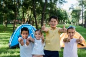 happy multicultural kids showing thumbs up near camps