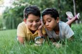selektivní zaměření roztomilých multikulturních chlapců ležících na trávě a dívajících se přes lupu