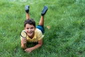cheerful boy lying on grass and holding magnifier