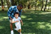 šťastný afroamerický otec dotek šťastného a roztomilým synem v zeleném parku