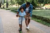 vousatý afroamerický otec pohled na kudrnatý syn jezdecký skútr