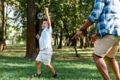 oříznutý pohled na otce ukazující prstem blízko šťastného afrického amerického syna gestikulovat v parku