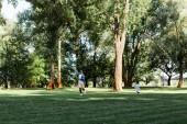 felice figlio afroamericano e padre in esecuzione sullerba nel parco