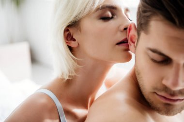selective focus of attractive and blonde woman kissing handsome man with closed eyes