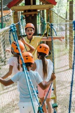 selective focus of cheerful boy near multicultural friends in adventure park