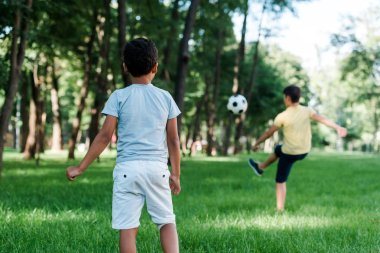 back view of african american kid standing near boy playing football