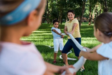 selective focus of happy multicultural kids competing in tug of war outside