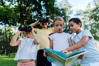 surprised kid looking at map with african american boy near friends with binoculars in park